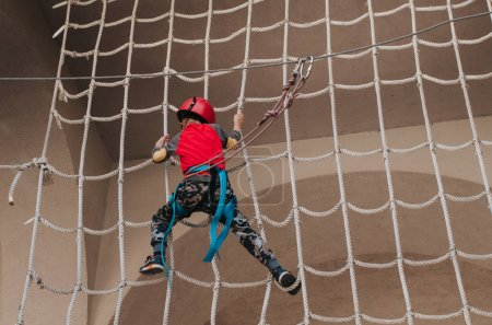 Photo for Boy in a helmet is engaged in an adventure rope park with all climbing equipment - Royalty Free Image