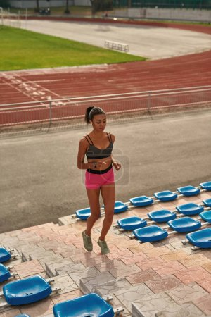 Photo for Full length shot of motivated young female runner training on the stadium outdoors. Sports, healthy lifestyle, fitness concept - Royalty Free Image