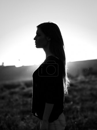 Woman silhouette in the sunset light. Black and white, artistic photography