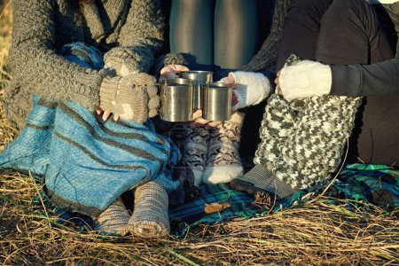 Girls in a warm knitted socks and with cups in the...