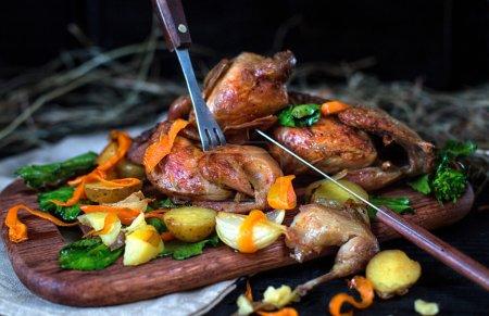 Photo pour Cailles rôties avec la pomme de terre, la carotte et les feuilles vertes de chou sur une planche en bois contre un backgroun foncé - image libre de droit