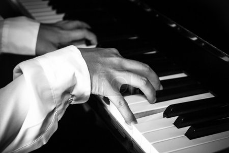 Hands of female pianist / musician playing piano B&W isolated on