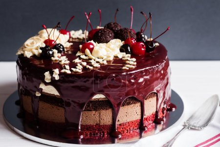 Photo pour Gâteau de couche décorés avec glaçage au chocolat, des fleurs crème et des cerises sur fond foncé - image libre de droit