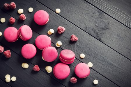 Photo for Pink macaroons with raspberries and white chocolate drops on black wooden background - Royalty Free Image