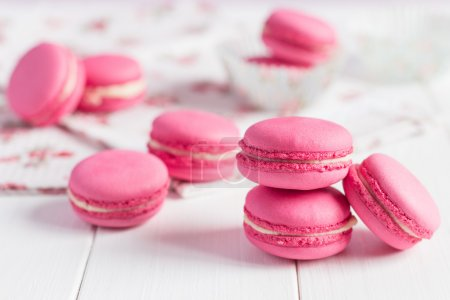 Photo for Some pink raspberry macaroons with cream ganache on white shabby chic wooden background - Royalty Free Image