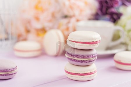 Photo for Pastel macaroons on pink table with defocused spring flowers and coffee cup on background. Shallow focus - Royalty Free Image