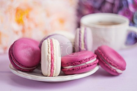 Photo for Colorful macaroons on pink table with defocused spring flowers and tea cup on background. Shallow focus - Royalty Free Image