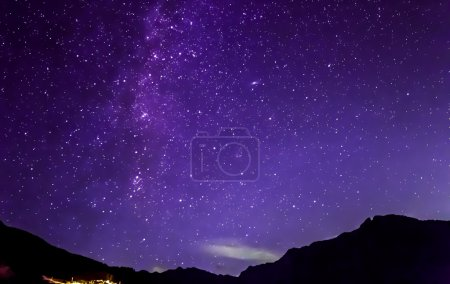 Photo for Purple night sky stars. Milky way across mountains - Royalty Free Image