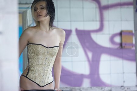 Girl with piercings posing  in a corset