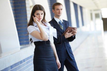 Foto de Joven empresaria con teléfono y hombre de negocios con tablet - Imagen libre de derechos