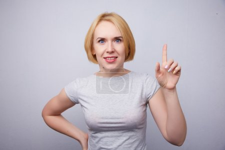 Beautiful young blonde woman points