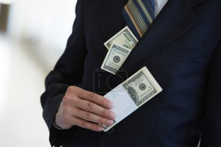 Money in pocket and hand of businessman