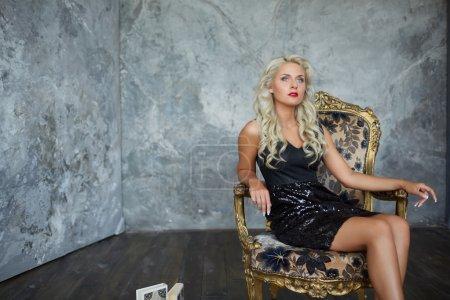 Glamouröse Frau im Vintage-Stuhl