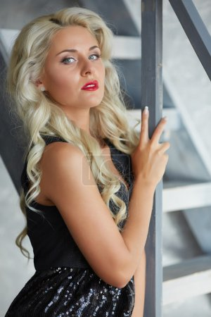 Photo for Attractive blonde woman posing near stairs - Royalty Free Image