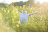 Happy boy in blooming meadow
