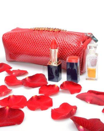 Photo pour Une rose rouge pétales, sac cosmétique cosmétique féminin, parfumerie dans la nature morte - image libre de droit