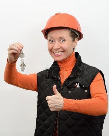Photo pour Ouvrier du bâtiment femme sourit et se réjouit à la main montrant les clés de la maison neuve - image libre de droit