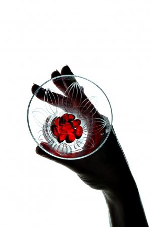 Silhouette of women hand holds fingers in transparent glass with a red glass of filler