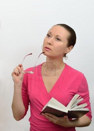 Photo pour Femme en lisant un livre et perdu dans la pensée a enlevé ses lunettes - image libre de droit