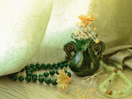 Green vase with bobby pins and hairpins, beads and a necklace of gemstones in still life