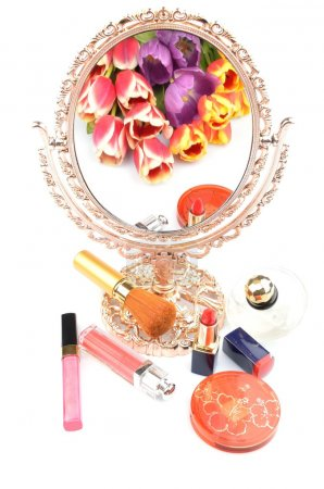 Antique gilded mirror reflecting a bouquet of flowers tulips and women's cosmetics and makeup on a white background
