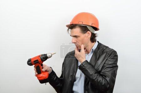 Photo pour Un homme travaillant dans la perplexité réfléchi regarder un pistolet à vis outil - image libre de droit
