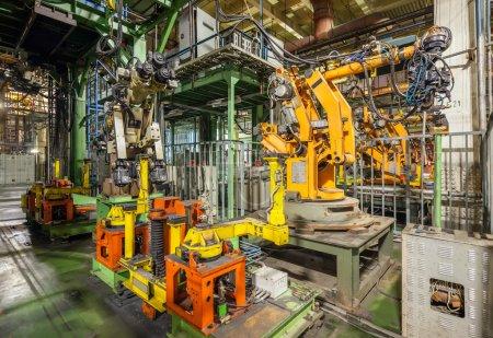 Photo pour Usine automobile en faillite et abandonnée. Robots jaunes soudant des voitures dans une ligne de production - image libre de droit