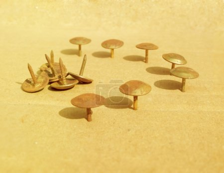 Foto de Pins pinned on the card board arranged in a half circle with some unpinned pins. - Imagen libre de derechos