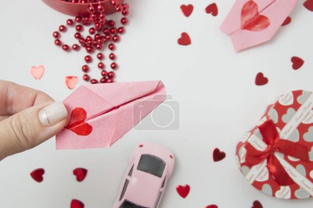 Photo for Pink car, red beads, pink plane, hearts and gift box on white background. valentine's day.hand in the picture. - Royalty Free Image