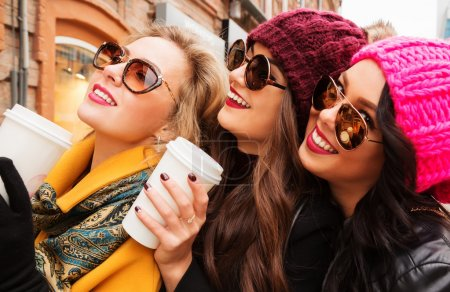 Close up portrait of three young cheerful pretty girls friends drinking coffee.  Smiling and going shopping.