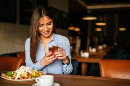 Photo pour Femme tenant un téléphone portable et profitant d'un petit déjeuner . - image libre de droit