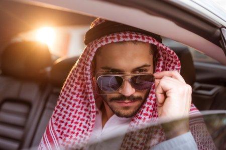 Photo pour Bel homme musulman posant dans la voiture . - image libre de droit
