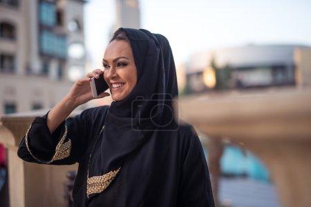 Beautiful muslim girl talking on a mobile phone....