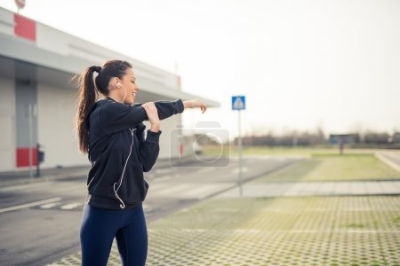 Photo for Young woman stretching arms before training. - Royalty Free Image