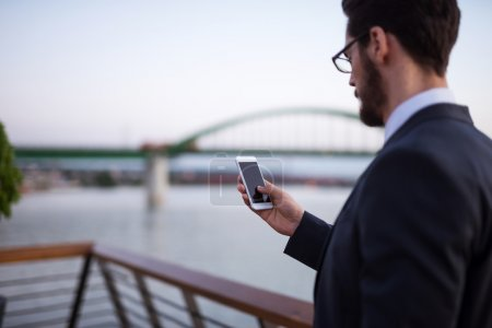 Photo for Handsome businessman texting on a mobile phone. - Royalty Free Image