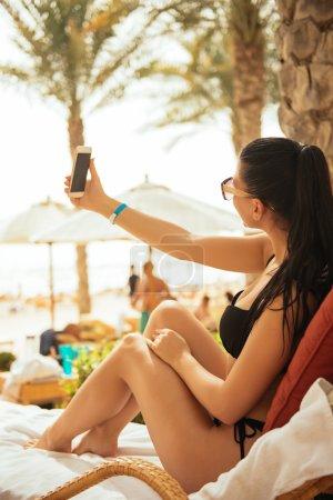 Photo pour Jeune fille attrayante dans un maillot de bain faisant selfie sur la plage . - image libre de droit