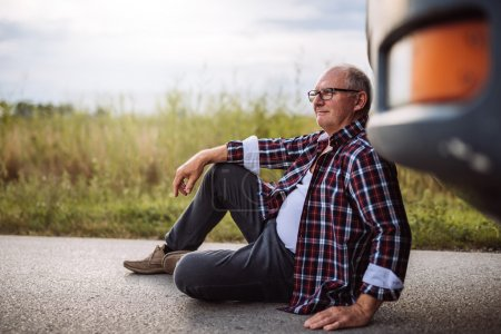 Photo for Senior truck driver sitting next to his truck. - Royalty Free Image