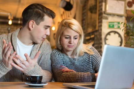 Photo pour Young couple sitting in the cafe with laptop making some important decisions. The foreground is blurred, narrow depth of field, natural and enviromental light. - image libre de droit
