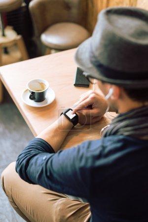 Photo pour Jeune homme élégant et à la mode vérifiant sa montre intelligente dans le bar du café. Plan grand angle. Concentration sélective. Image tonique . - image libre de droit