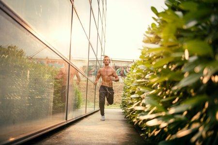 Photo pour Jeune homme jogging à côté du centre sportif moderne, écouter de la musique avec son casque. Porter des survêtements sans chemise. Image tonique, lumière directe du soleil, fusée éclairante . - image libre de droit