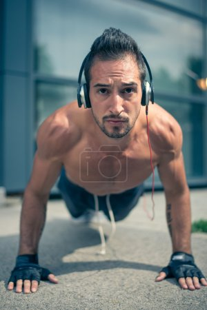 Photo pour Young male listening to the music and doing push ups in front of the modern sport centar. Selective focus. - image libre de droit