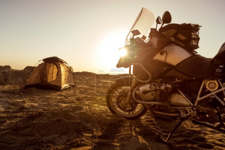 Photo for Sunset moment. In the background tent and motorbike. Toned image. Lans flare - Royalty Free Image