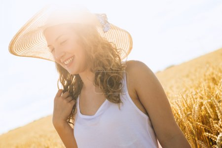 Photo pour Belle jeune fille avec son chapeau, debout dans le champ de blé au coucher du soleil. Concentration sélective. tonique dans des couleurs chaudes . - image libre de droit