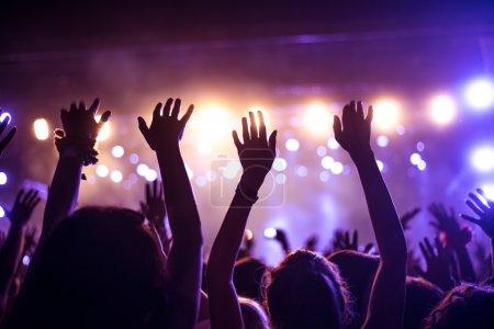 Photo pour Une foule de gens célébrant et faisant la fête avec leurs mains en l'air à un DJ impressionnant. Image granuleuse ISO élevée . - image libre de droit