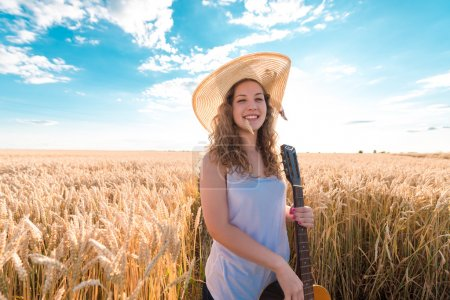 Photo for Beautiful young girl with her hat on, standing in wheat field at sunset. Selective focus. Toned in warm colors. - Royalty Free Image
