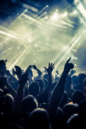 Photo pour Une foule de gens célébrer et faire la fête avec leurs mains en l'air pour une image granuleuse de génial Dj. High Iso. Flou artistique. - image libre de droit