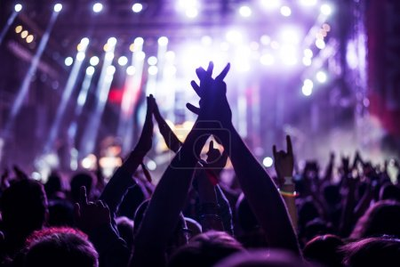 Photo for Audience with hands raised at a music festival and lights streaming down from above the stage. Soft focus, blurred movement - Royalty Free Image