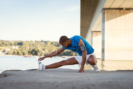 Photo for Young male athlete streching next to the river after morning work out - Royalty Free Image
