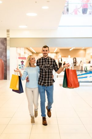 Photo for A shot of a smiling young couple with their shopping bags. Selective focus. - Royalty Free Image