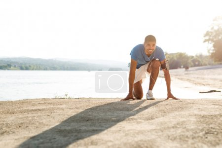 Photo for Shot of a young male athlete at the start position next to the river. - Royalty Free Image